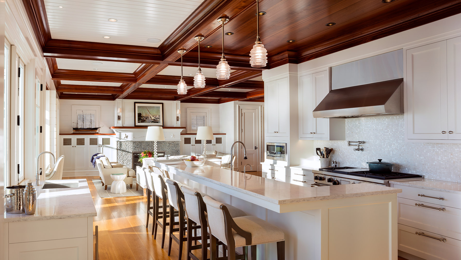 New kitchen design with mahogany coffers, beadboard paneling, breakfast island with sink, stainless steel appliances, oak flooring, wine bar, high top chairs, river rock fireplace, white walls, brass hardware, bee hive pendant light fixture.